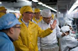 Apple chief executive Tim Cook (C-L) visits the iPhone production line at the newly built Foxconn manufacturing facility