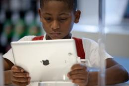 A Brazilian boy looks at an iPad