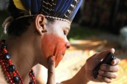A Brazilian Indian makes up before the inauguration of the People's Summit
