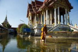 A Buddhist monk cleaning up an area at a temple inundated by flood waters in Don Muang district, in Bangkok, in 2011