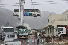 A bus was removed from the roof of a building in Ishinomaki on the day after the March 11 earthquake-tsunami disaster