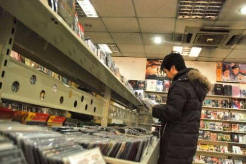A customer is seen selecting pirated DVDs at a shop in Beijing, on January 2, 2010