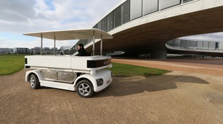 A driverless electric shuttle makes its way through the EPFL campus