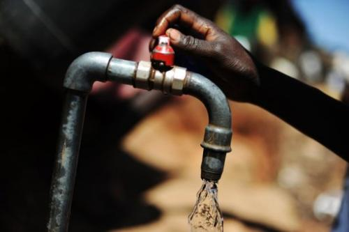 A Kenyan woman turns on a tap at a water distribution site in the Kibera slum of Nairobi