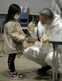 A little girl holds out her hands for a radiation scan at a screening center in Koriyama in Fukushima prefecture