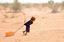 A Malian refugee pulls a jerry-can of water in Mauritania