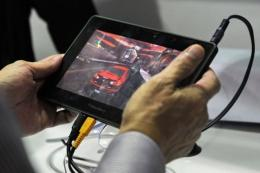 A man plays an online game with a Blackberry PlayBook