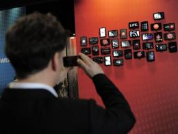 A man takes pictures with his mobile phone at the Mobile World Congress in Barcelona