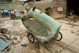 A man uses a bicycle to transport a sofa chair in Tomana slum