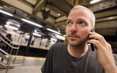 A man uses his cell phone in a subway station in New York