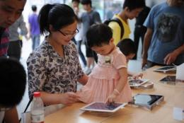 A mother and daughter play with an Apple iPad at an Apple store in Shanghai