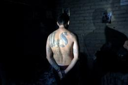 An alleged gang member is handcuffed in Mejicanos, a suburb of San Salvador