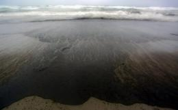 An oil slick stains a New Zealand beach in 2011