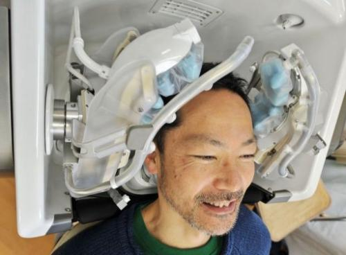 A prototype of a high-tech head massager is tested out by a Japanese tsunami survivor