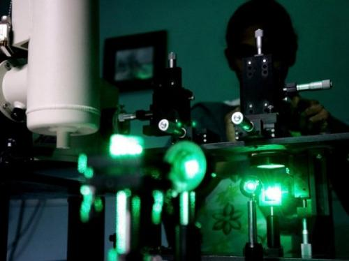 A research scholar experiments with laser rays in a lab