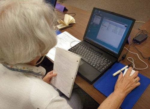 A senior citizen works on her laptop during a computer class