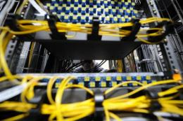 A telecommunications specialist mounts data storage equipment