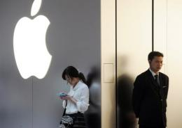 A woman (L) uses her mobile phone as a security guard looks on outside an Apple store in Shanghai