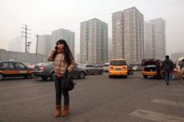 A woman talks on a mobile phone as she stands on a roadside before high-rise apartments in Beijing