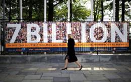 A woman walks past a UN sign announcing symbolically that the world population hit 7 billion in 2011