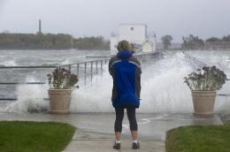 A woman watches waves crash onto a pier on City Island in New York