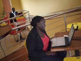 A woman works on her laptop at an internet cafe in Kampala