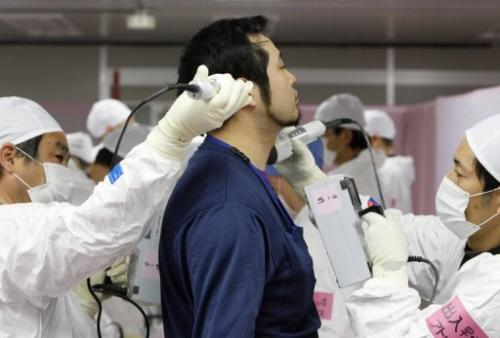 A worker is screened for radiation before entering the emergency operation centre