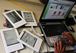 A worker uses a laptop as he uploads e-books in Bangalore