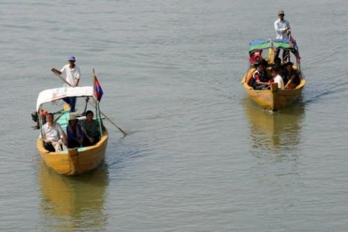 Cambodian and foreign tourists on boats to spot dolphins along the Mekong river on December 6, 2012