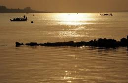 Cambodian fishermen row their boats on the Mekong river in Phnom Penh on March 2