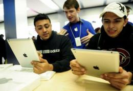 Customers look at the a new Apple iPad at Apple's store in New York