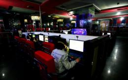 Customers use computers at an internet cafe in Hami, northwest China