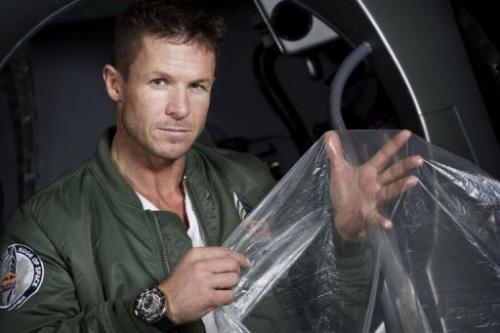 Felix Buamgartner of Austria shows a piece of the balloon material