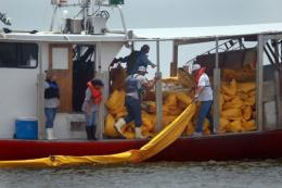 Fishermen use their shrimp boat to place oil booms into the water in May 2010 near Shell Beach, Louisiana