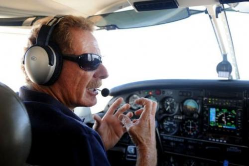 Gerard Moss talks as he flies the small plane he uses for his