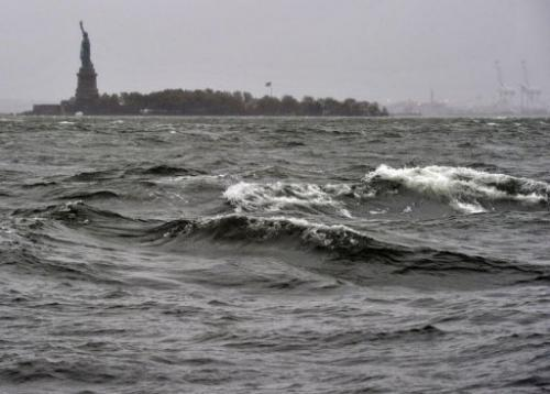 High surf batters the Hudson River near the Statue of Liberty in New York