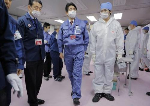 Japan's new PM Shinzo Abe (C) visits the crippled Fukushima Daiichi nuclear power plant in Ota, on December 29, 2012