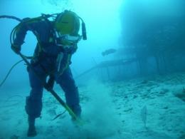 NASA file image shows a NEEMO 14 aquanaut practicing shoveling underwater