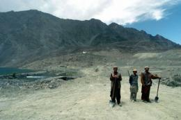 Pakistani labourers stand with mountains of the Himalayan Karakoram range