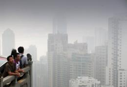 People look across the Hong Kong skyline shrouded by smog