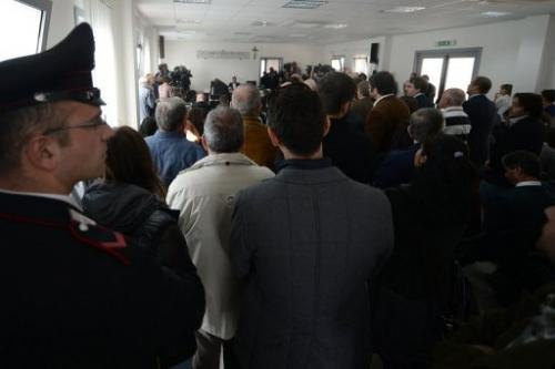 People stand as court proceeds in L'Aquila, Italy