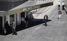 People walk past Goldman Sachs headquarters