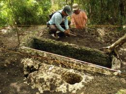 Philippine archaeologists work on an unearthed limestone coffin