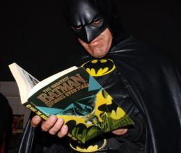 Superhero Batman reads a Batman comic book