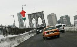 Taxis and cars make their way over the Brooklyn Bridge
