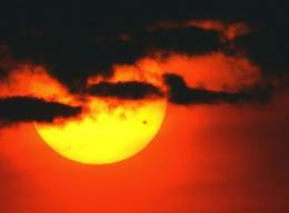 The sun rises through clouds as the planet Venus (dot on lower right of sun) crosses its face