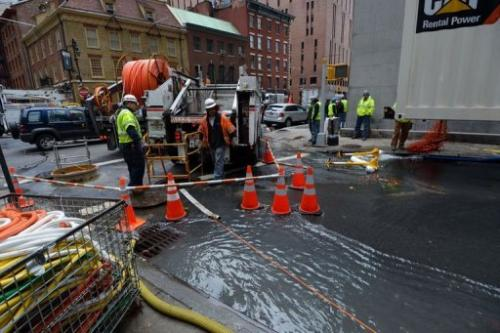 Work crews from Verizon pump water from an access tunnel in Lower Manhattan