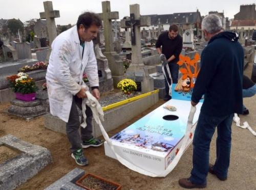 Workers install an 'iron grave' at a cemetery in Nantes for TV show creator Serge Danot who died in 1990