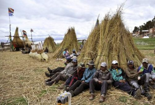 Workers take a break from building a bulrush boat on Suriqui island in Lake Titicaca, Bolivia,  December 2, 2012
