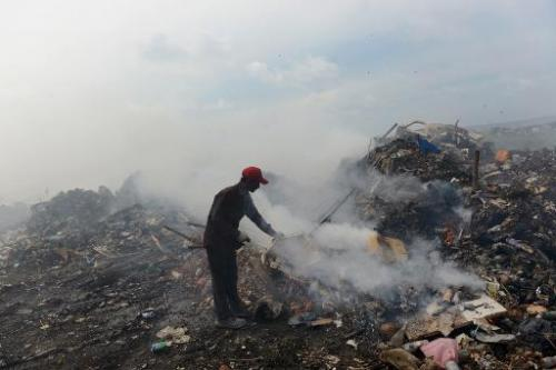 A Bangladeshi immigrant helps keep a fire going in the country's largest trash dump at Thilafushi Island on September 6, 2013